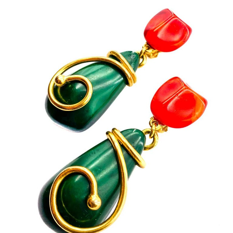 The earrings are from the House of YVES SAINT LAURENT. These are hanging clips, orange-red at the clasp, green covered with gold metal on the pendant side. The clips are in very good condition despite a trace on the top of the pendant of one of