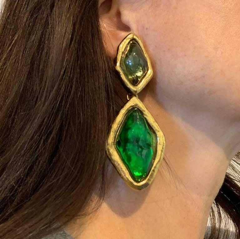 Find all the essence of the House SAINT LAURENT with these magnificent dangling earrings which gather on a base gilded with fine gold, cabochons of green resin.  The clips are in a very good condition. The gilding is impeccable, we do not notice any