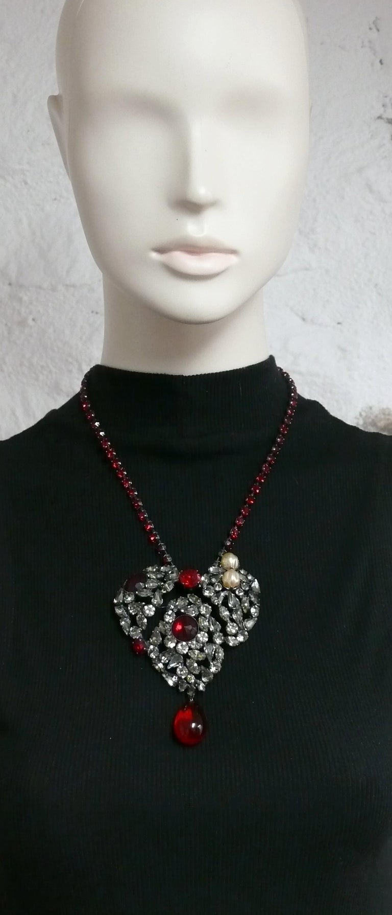 YVES SAINT LAURENT vintage massive iconic pendant necklace featuring a gun metal patina heart embellished with light grey and red crystals, faux pearls, red glass drop and a ruby rhinestone chain.  Similar model worn by LAETITIA CASTA on the catwalk