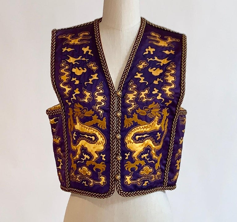 Yves Saint Laurent Rive Gauche 1960s or 1970s vintage satiny purple cropped waistcoat vest which has been embroidered and cut away to reveal a gold dragon print. Gold braided trim and beautiful black and gold buttons with loop closures. Documented,