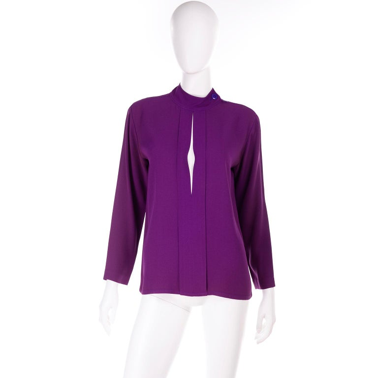This vintage Yves Saint Laurent purple silk crepe top has a diamond cutout in the front with a buttoned high neck.  This long sleeve blouse was made in France and is labeled size 36. There is a metal zipper on the right shoulder with button at the