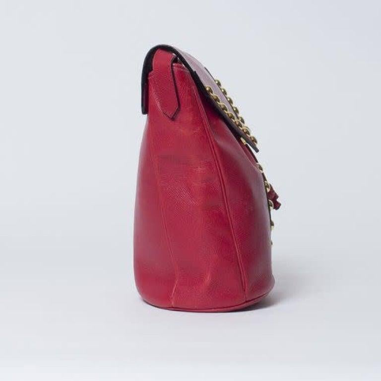 This vintage YSL bag is made with red leather with gold-tone studs at front forming the letter Y. Featuring drawstring closure, gold-toned hardware, black interior lining, and an interior zip pocket.  COLOR: Red MATERIAL: Leather ITEM CODE: Vintage