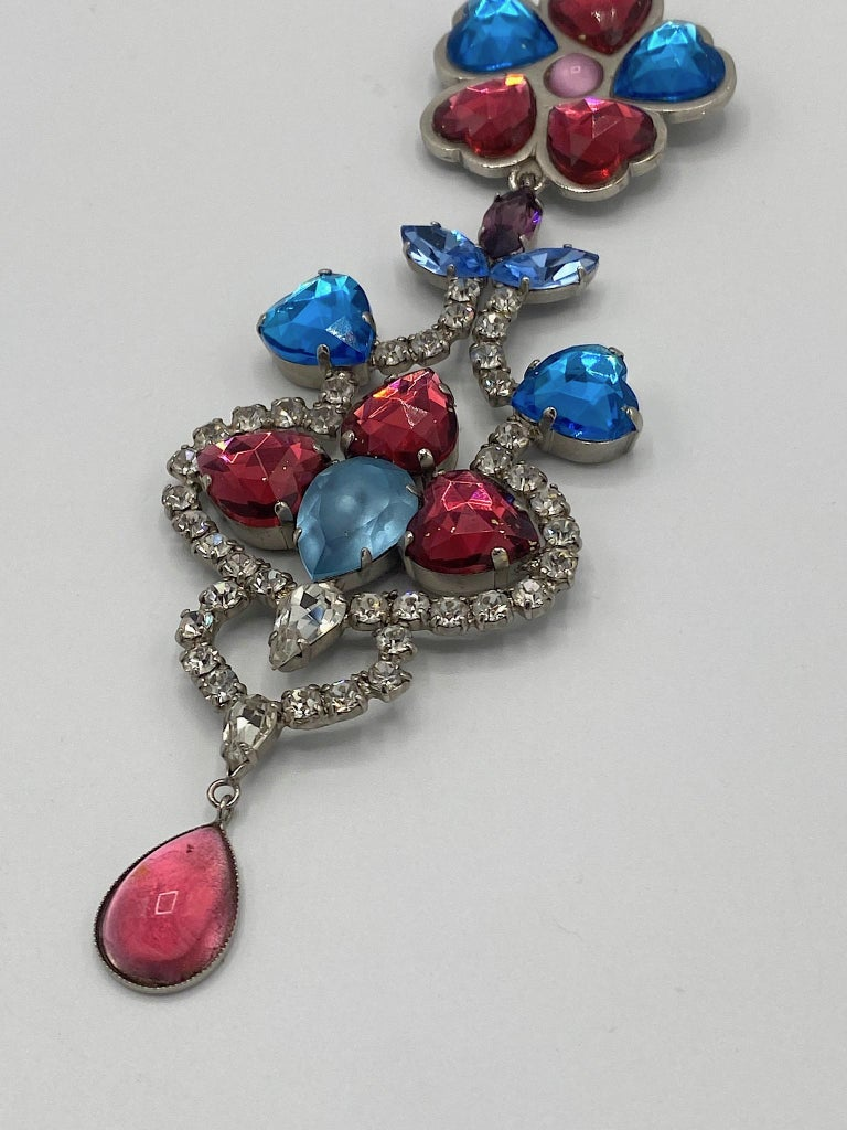 A wonderful example of Yves Saint Laurent creativity in fashion jewelry design is this 1980s 6.25 inch long brooch. The top piece features five faceted teal and deep rose color crystal heart rhinestones half an inch wide and .63 of an inch long