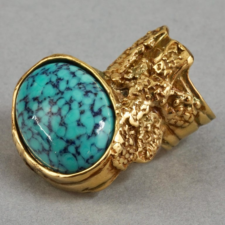 YVES SAINT LAURENT YSL Arty Turquoise Ring  Measurements: Height: 1.49 inches (3.8 cm) Width: 1.18 inches (3 cm) Size: US6  Features: - 100% Authentic YVES SAINT LAURENT. - Textured ring with turquoise cabochon stone. - Gold tone. - Signed YVES