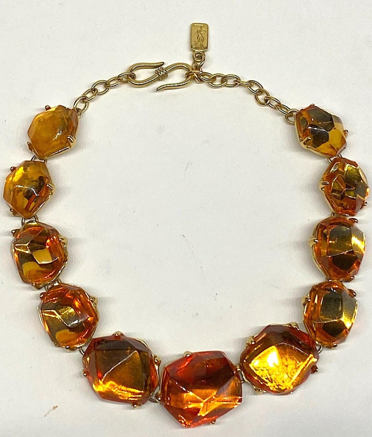 A beautiful 1980s Yves Saint Laurent necklace by famous French designer Robert Goosens. The necklace is comprised of 11 poured and faceted golden honey amber color resin stones. The stones are mounted into gold plate settings and linked together.