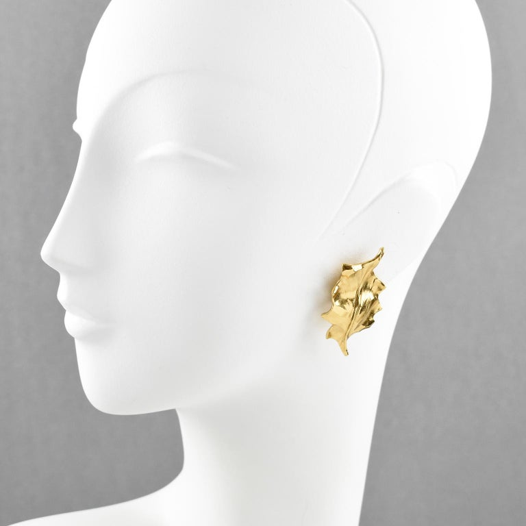 Elegant Yves Saint Laurent YSL Paris Leaf clip-on earrings. Featuring gilt metal bold floral shape with a holly leaf, metal all textured with dimensional carved design. Signed at the back 'YSL, Made in France'.  Measurements: 1.82 in. high (4.6 cm)
