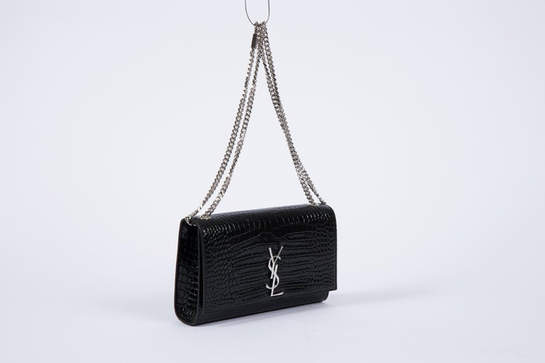 YSL Yves Saint Laurent black patent crocodile embossed handbag with silver tone hardware. Can be worn shoulder length or cross body. Comes with booklet and original dust cover.