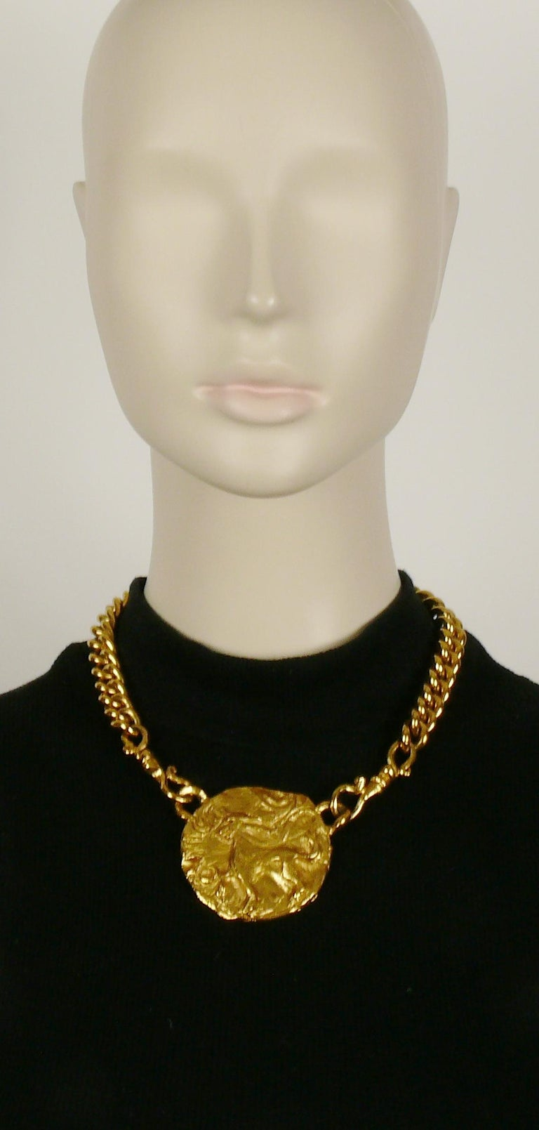YVES SAINT LAURENT vintage gold toned chunky chain necklace featuring a raised and textured mythological creature medallion.  Toggle and hearts closure with YVES SAINT LAURENT signatures. Adjustable length.  Embossed YVES SAINT LAURENT on the heart