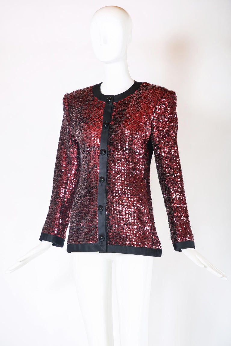 Vintage Yves Saint Laurent dinner jacket covered with reddish/dark pink sequins and trimmed with black silk. Features oversized black dome-shaped buttons and is lined in silk at the interior. Tag size 38 but please consult measurements as vintage