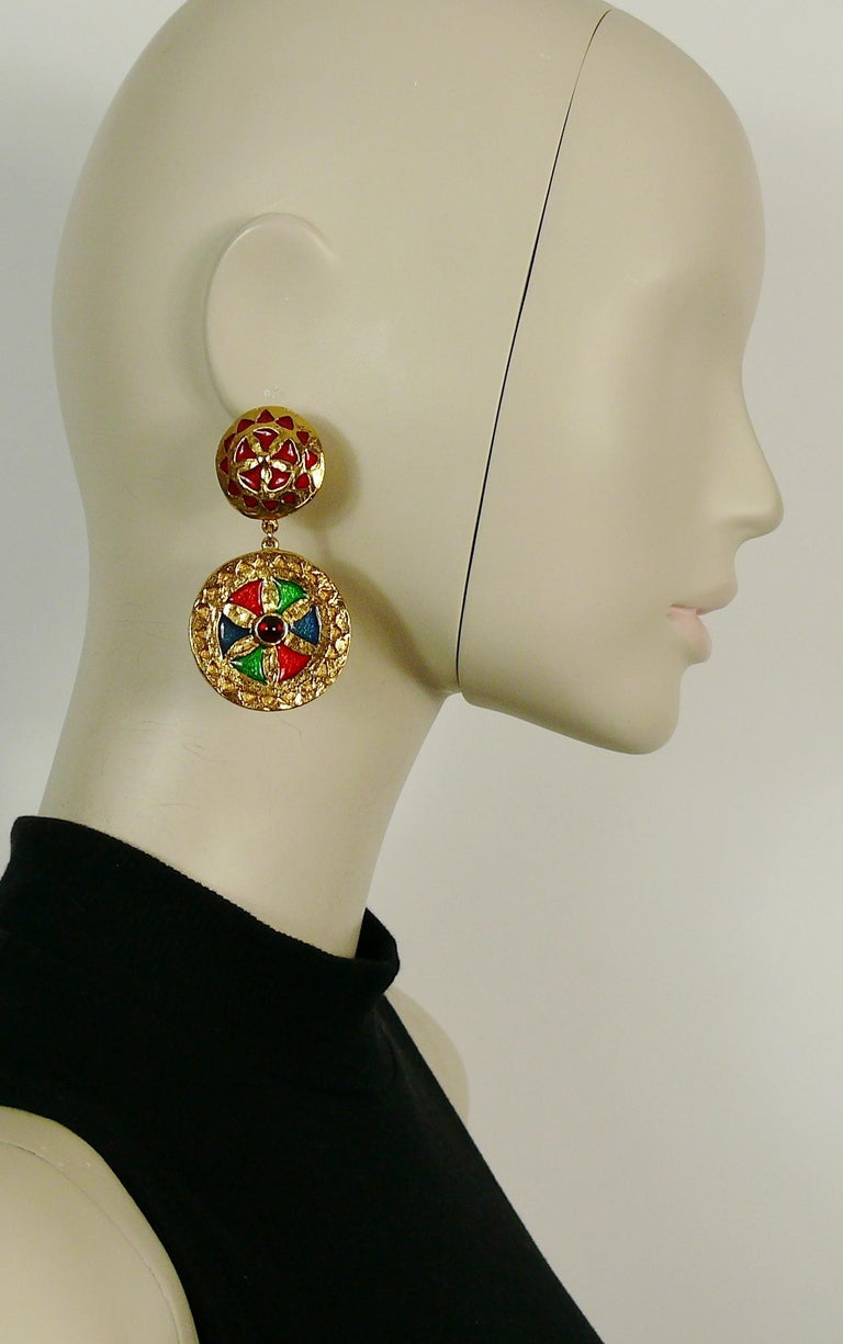 YVES SAINT LAURENT vintage gold toned dangling earrings featuring shields embellished with multicolored enamel and red glass cabochon.  Marked YSL. Made in France.  Indicative measurements : height approx. 7.1 cm (2.80 inches) / max. diameter