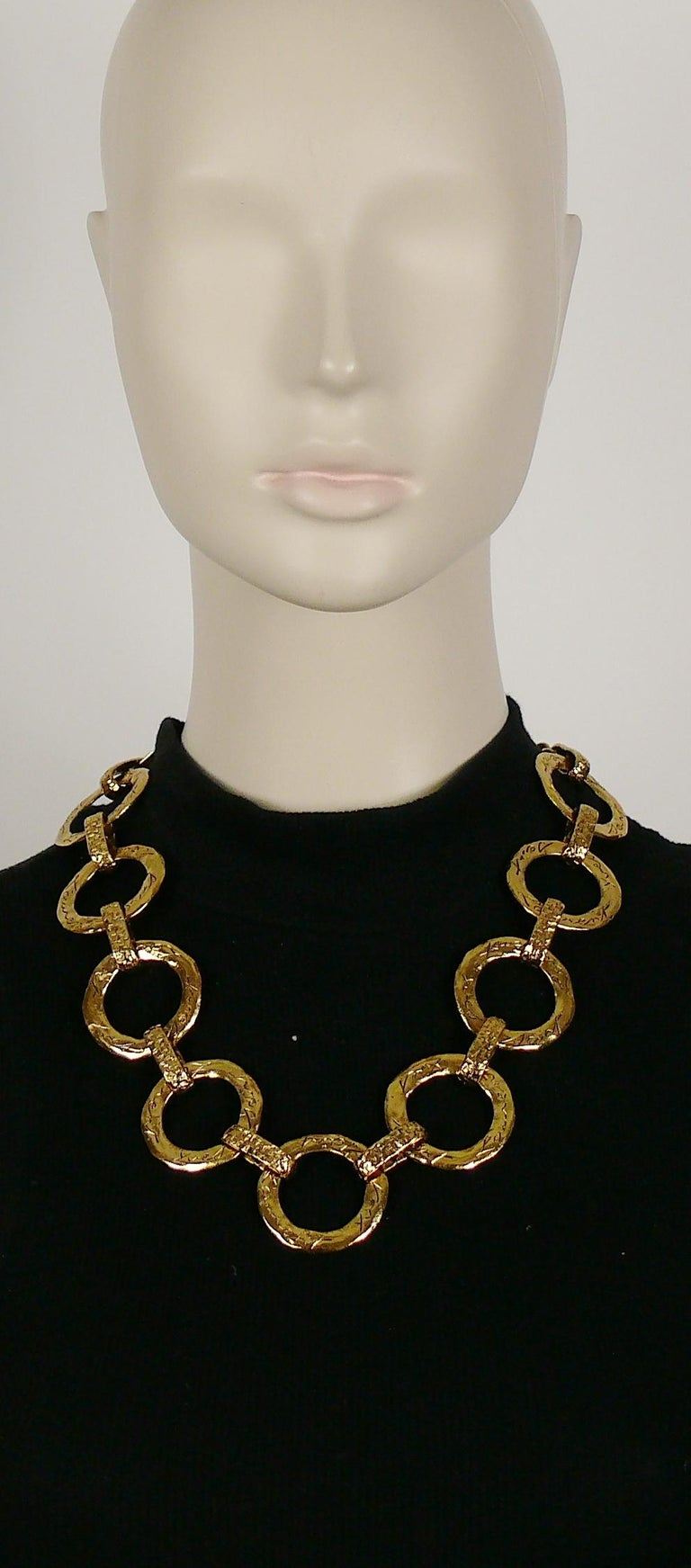 YVES SAINT LAURENT vintage gold toned necklace chunky textured circle links.  T bar and toggle closure. Adjustable length.  Embossed YVES SAINT LAURENT cursive signature on the toggles. Made in France.  Indicative mesaurements : adjustable length