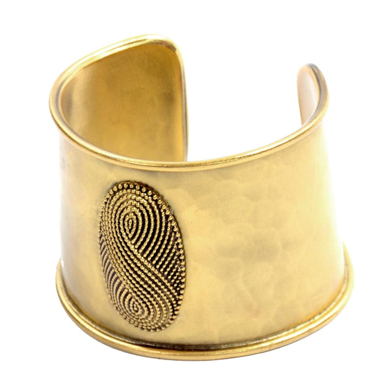 This is a wonderful vintage cuff bracelet from Yves Saint Laurent.  The bracelet is in a gently hammered gold metal with an interesting textured design in an oval on the front.  Signed Yves Saint Laurent, this piece measures 2