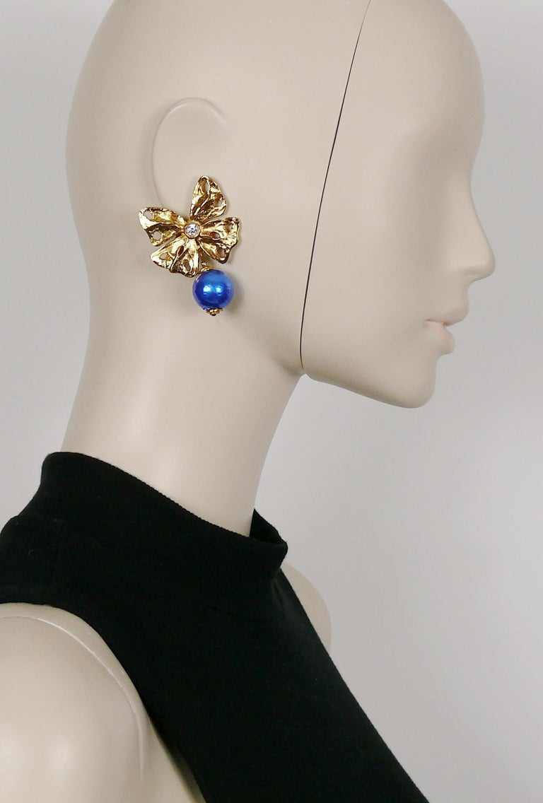 YVES SAINT LAURENT vintage textured gold toned butterfly dangling earrings (clip-on) embellished with a clear crystal center and a large blue dangling ball charm.  Embossed YSL Made in France.  Indicative measurements : max. height approx. 5.3 cm