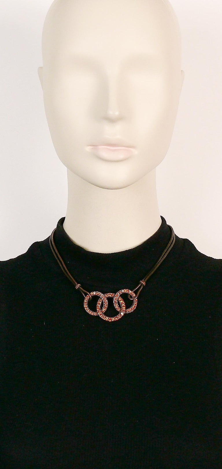 YVES SAINT LAURENT vintage antiqued copper toned necklace featuring a double snake chain and three intertwined rings embellished with citrine color crystals.  Adjustable T-bar and toggle closure.  Embossed YSL Made in France.  Indicative
