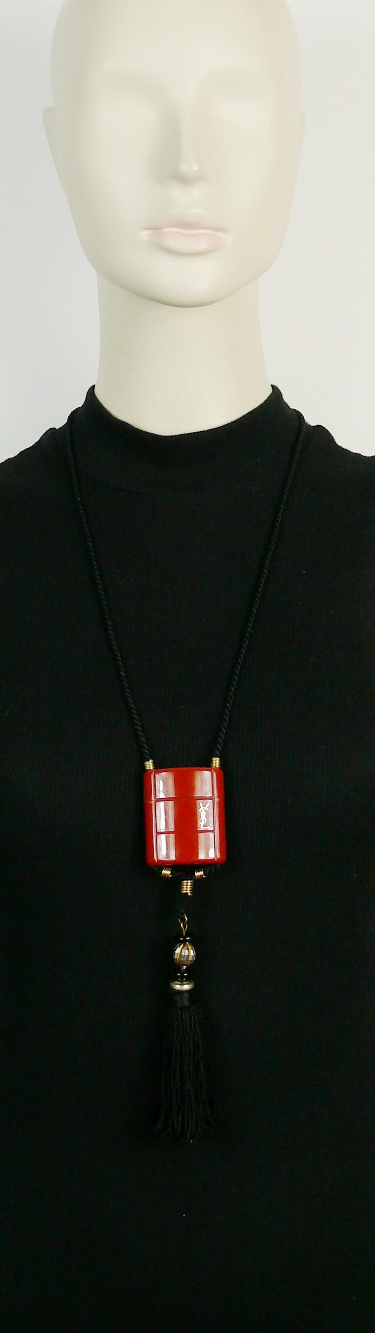 YVES SAINT LAURENT vintage OPIUM inro pendant necklace.  This necklace consists of a black cord, a burnt orange plastic container, a silk tassel adorned with black and gold tone beads.  Plastic container opens to insert a miniature bottle (empty
