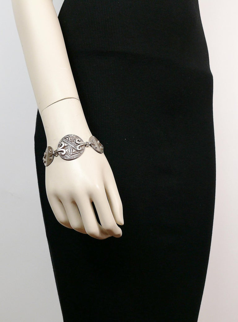 YVES SAINT LAURENT vintage antiqued silver toned disc links bracelet featuring tuareg pattern inspired engravings.  T-bar and toggle closure.  Embossed YSL Made in France.  Indicative measurements : length approx. 19 cm (7.48 inches) / max. width