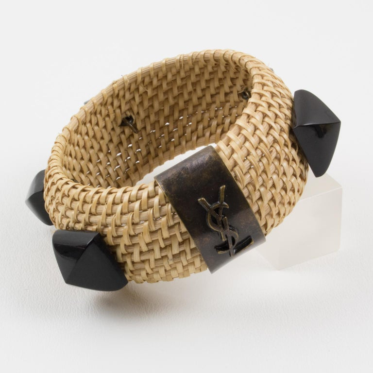 A splendid Yves Saint Laurent YSL Paris bangle bracelet. Featuring a stunning combination of tribal bronze age with on-trend wicker. Heavily domed bangle shape with braided wicker studded with domed faceted licorice black high relief cabochons and