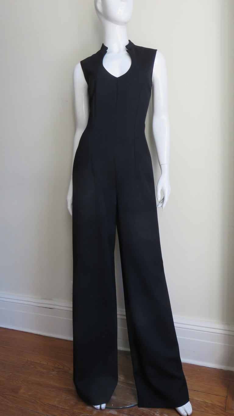A fabulous black wool jumpsuit from Yves St Laurent YSL A/W 2010 collection.  It is sleeveless with a circular front cut out at the neck and a stand up collar.  It is semi fitted with wide legs,  unlined and has a center back zipper. Fits sizes