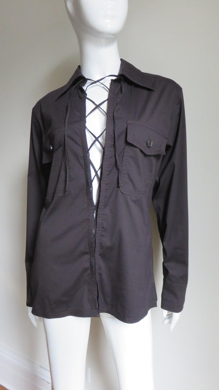 A rich brown fine cotton shirt from Tom Ford for Yves St Laurent, YSL.  It has a shirt collar, button flap front patch chest pockets, a back yoke, and matching button cuffs.  There is elaborate functional, adjustable lacing along the center front.