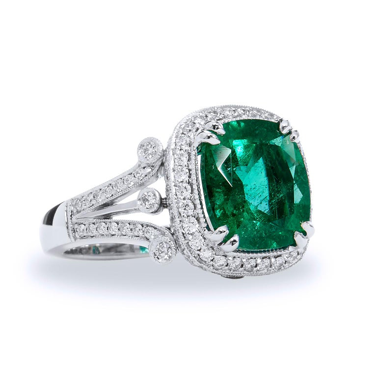 Zambian Cushion Cut Emerald Diamond Ring  This stunning emerald and diamond ring is handmade and one of a kind.  The center stone is a 4.09 carat Zambian emerald.  It is surrounded by 100 pieces of 0.7 carat diamonds that are G/H in color and VS in