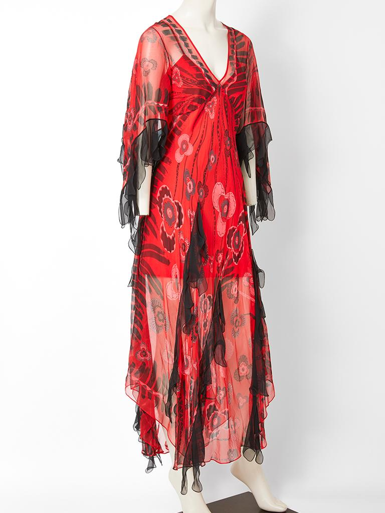 Zandra Rhodes, red chiffon, bohemian style, midi dress with a black iconic Rhodes print. Dress has an empire waist with a deep v neck and bat wing sleeves. Black tulle at the sleeve hem and vertically placed on the dress body adds to the whimsical