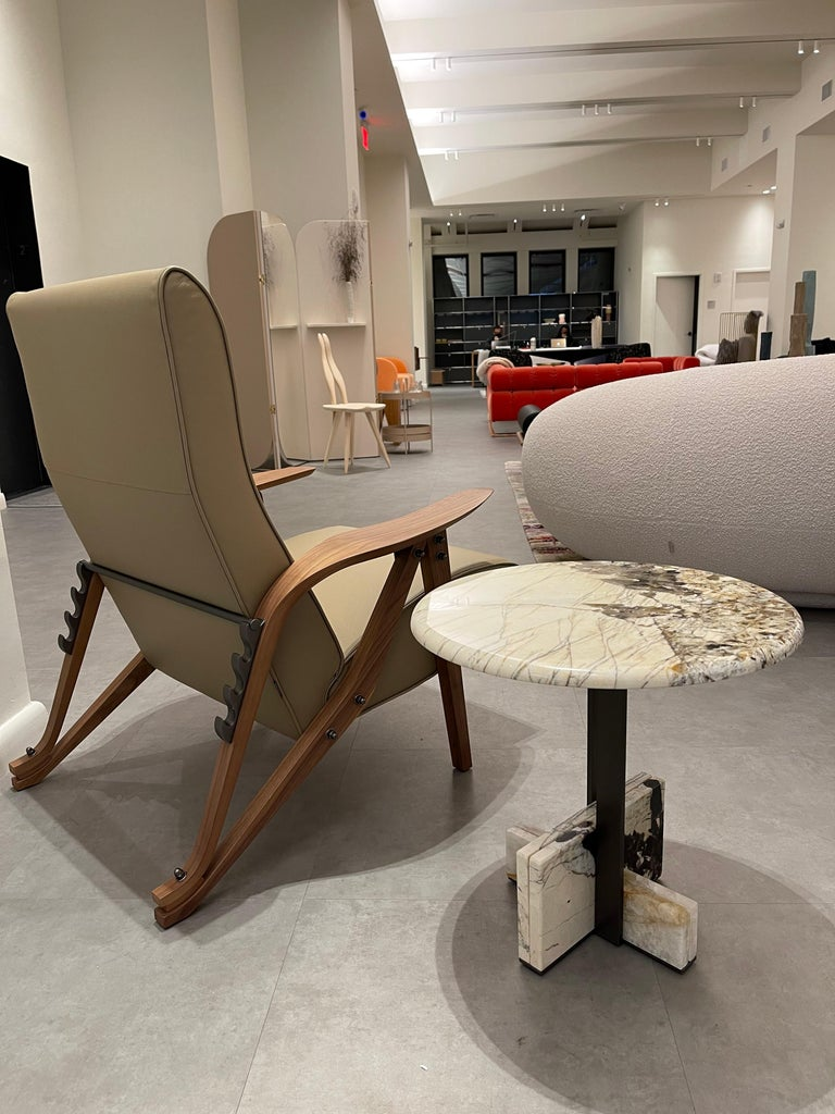 A reclining armchair with four positions, which represents Mollino's eclectic style, seeking ergonomics and comfort.  Details and elegance: shaped solid wood and a single element that joins the legs and the cozy armrest, similar to a leaf, large