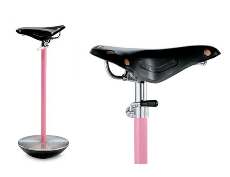 Seat. Black saddle of racing bicycle, pink lacquered steel column. Cast iron base. he object was designed as a 'telephone stool' for unusual postures and occasional sitting, but besides its clear reference to the world of bicycle races (its colour