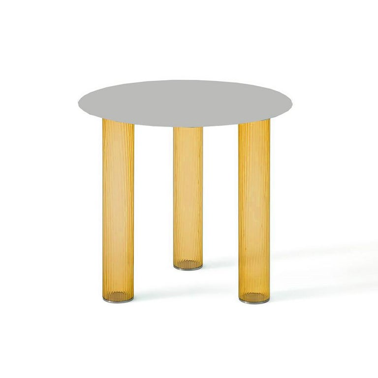 Small tables. Three-layered blown glass legs in amber and blue. Sebastian Herkner, renowned for his particular sensitivity toward glass, designed a pair of small tables where the glass strength and durability are axiomatically used for developing