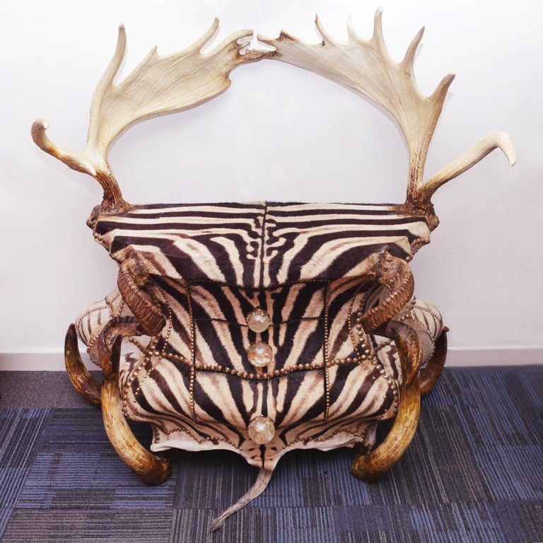 Chest of drawers Zebra and Elk with structure in solid beech wood and covered with real zebra skin. With 3 drawers, with real zebu and aries horns, with 2 real elk wood. Handles in rock crystals. Nails, details and finishes in solid bronze.