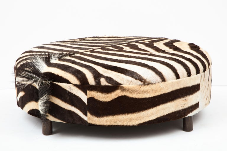 Decorative zebra hide ottoman. Zebra hide is from South Africa and the ottoman is made in NJ. Measures: diameter is 36 inches and height is 12 inches. The mane of the zebra is very decorative located on the side of the ottoman. The ottoman has four