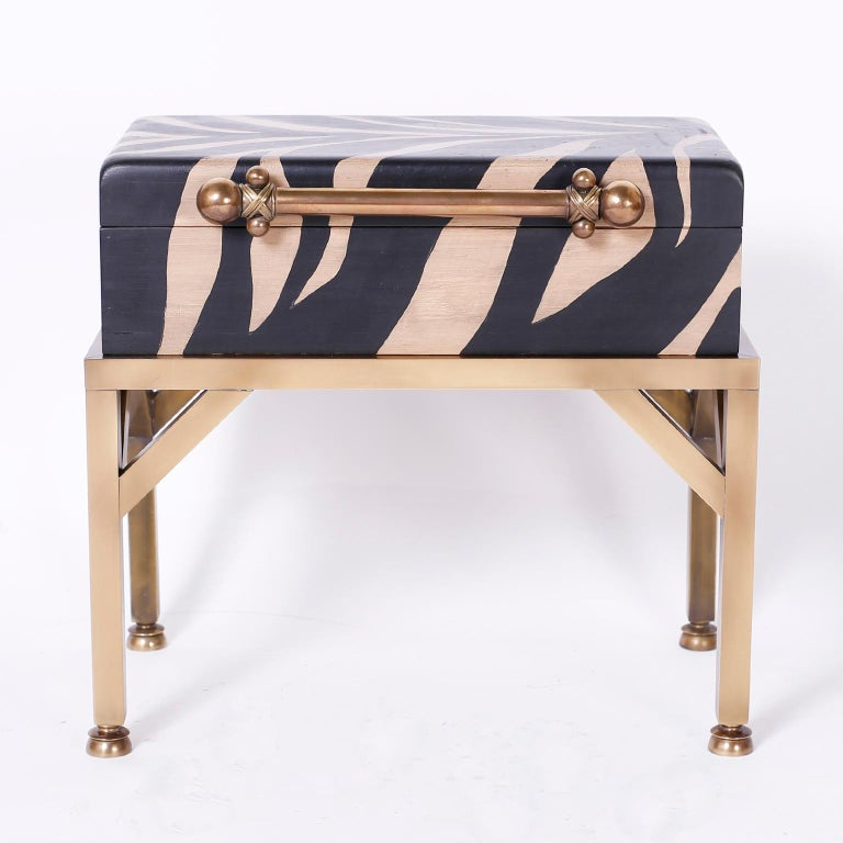 Midcentury lidded wood box decorated in faux zebra paint with a decorative handle and set on a burnished brass stand.