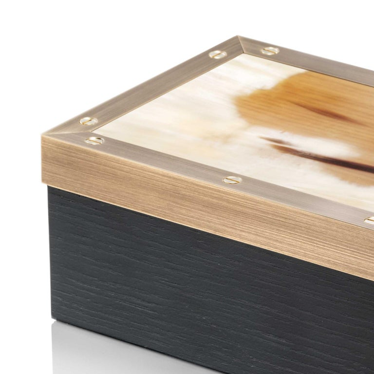 Contemporary style and high quality materials distinguish our Zefiro box, handcrafted from black oak veneer. An impressive lid in matte brown grained Corno Italiano with edging in burnished brass and 24-karat gold-plated screws elevates the