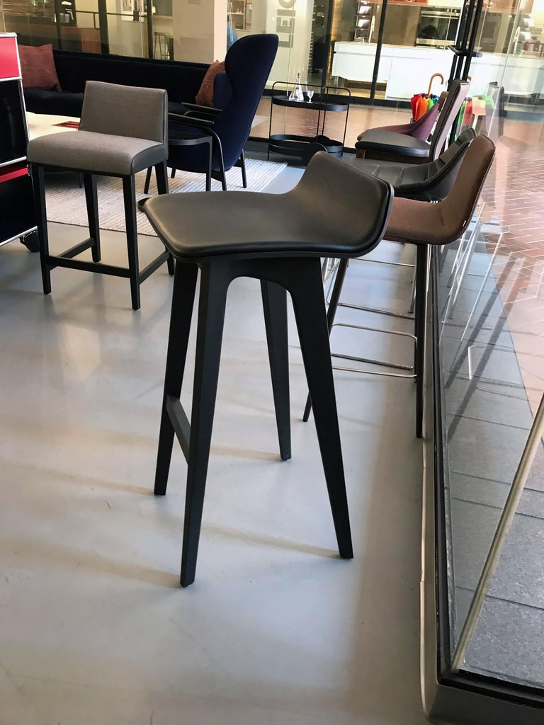 Oak color stained black/ black leather upholstered seat Thanks to the shape of the seat and its ideal incline, Morph Stool is more comfortable than one would expect. Formally, he has a unique feature, looks elegant and fits many