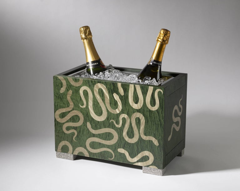 Designed as a companion piece to Zelouf & Bell's Champagne Cart, the Serpent Champagne Cooler in hedge green bird's-eye maple features a graphic marquetry serpent motif inlaid in figured muted grey-green ripple sycamore. While seated on ink