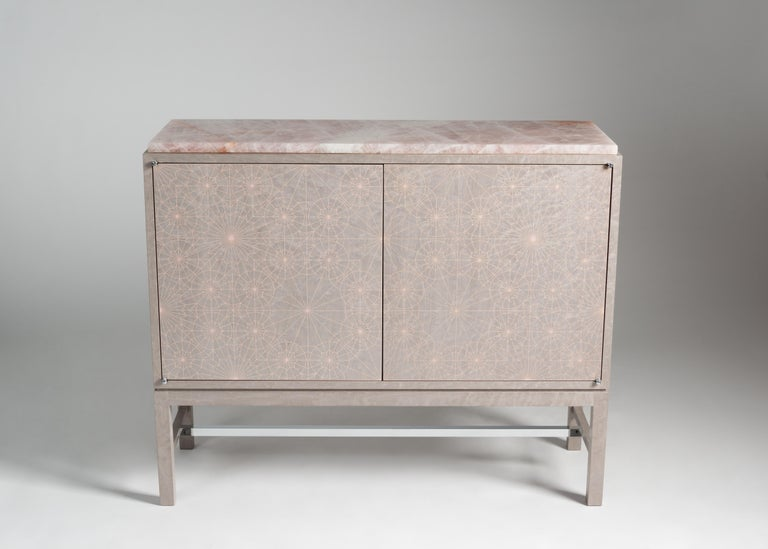 Zelouf & Bell's two-door constellation cabinet in a dusty pink-infused grey bird's eye maple features a delicate web of tone-on-tone marquetry in pink ripple sycamore, a secondary top in rose quartz, and a pink ripple sycamore interior with shelves