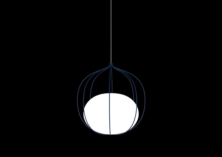 The Hoop pendant incorporates a metal cage-like frame made up of eight wires. Inside the frame, a globe-shaped glass diffuser rests at the bottom. The minimalist design and organic shape of this fixture is achieved by having the electrical wire fed