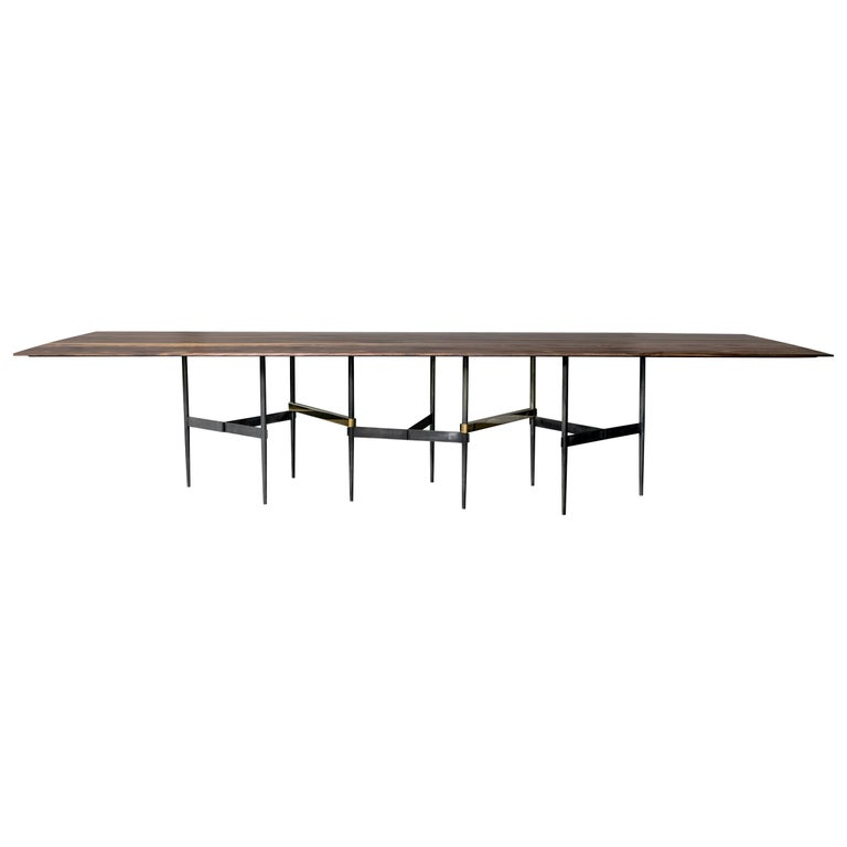 Zig Zag table in walnut and brass by Atra.  The Zig Zag table, part of the 2018 collection is part of the new series released by Alexander Diaz Andersson. The legs form a beautiful zigzag pattern in blackened bronze with polished brass bars. With a