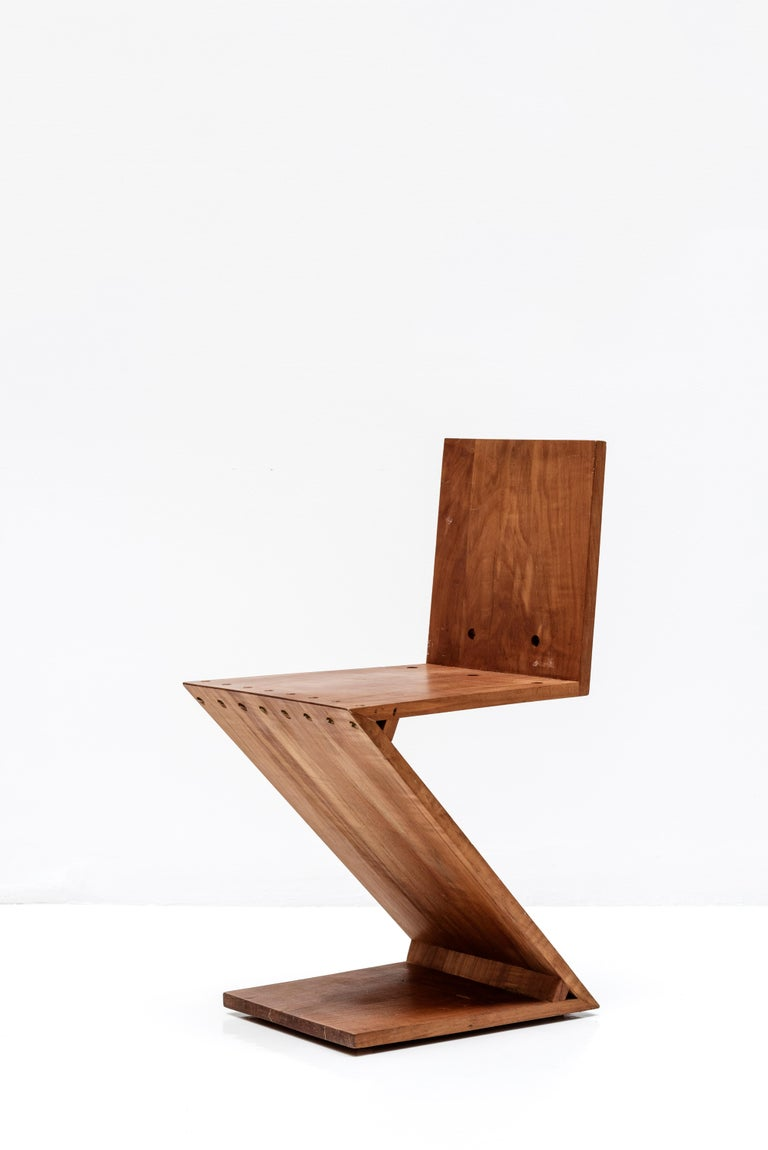 Zig-Zag chair designed Gerrit Rietveld. It's a minimalistic design without legs, made by 4 flat wooden tiles that are merged in a Z-shape.  Made of elm and brass.  Netherlands, circa 1960.  (Designed in 1934 by Gerrit Rietveld).