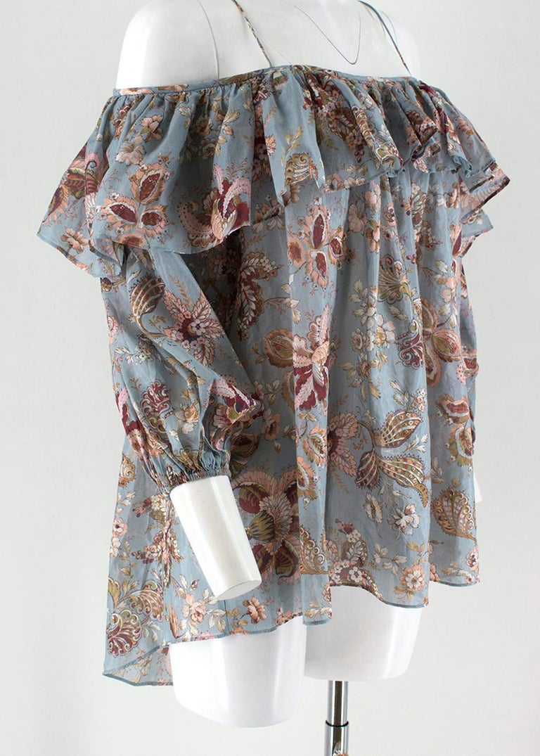 Zimmermann Pavilion off-the-shoulder top  -Blue floral, cotton blend -open-shouldered long sleeve -Ruffled around neckline and shoulders -Spaghetti strapping   Please note, these items are pre-owned and may show some signs of storage, even when