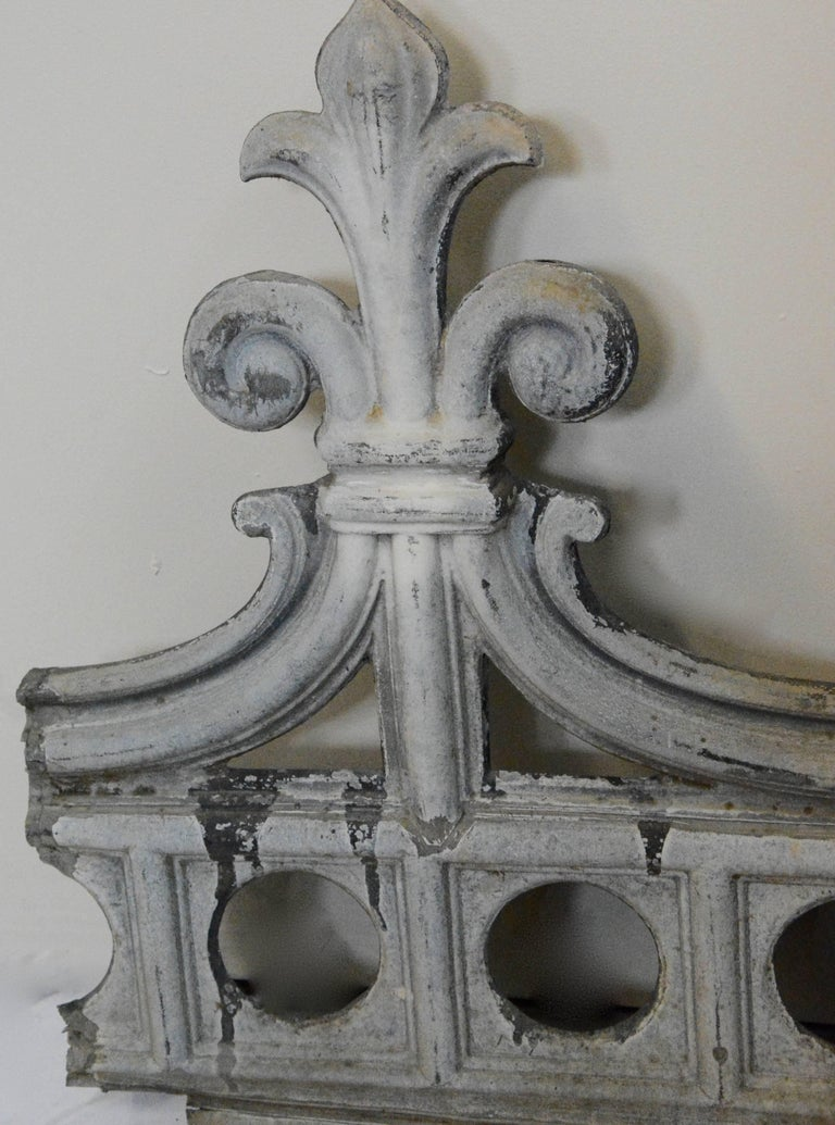 Featured is a nice metal architectural fragment that will make a unique wall decor piece. This piece features a row of circular cutouts topped with elegant curves and uprights with fleur-de-lis finials. There are no apparent maker's marks, and