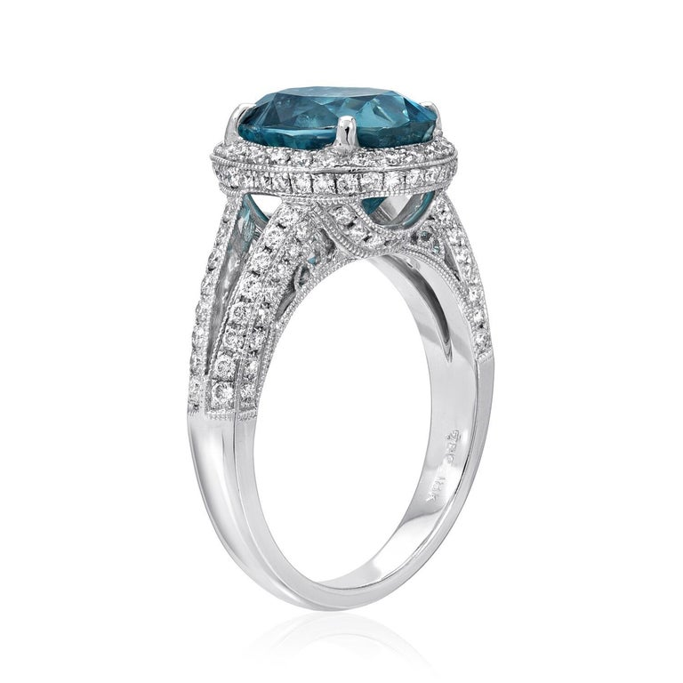 Vibrant 6.07 carat oval Zircon, adorned by round brilliant diamonds weighing a total of 1.00 carats, in this striking 18K white gold cocktail ring or engagement ring for women. Ring size 6.5. Resizing is complimentary upon request.  Returns are