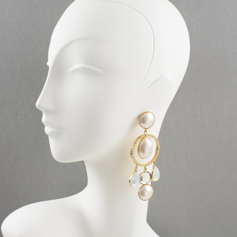 Lovely Zoe Coste signed chandelier clip-on earrings. Featuring an elegant large gilt metal framing dangling composition with pearl-like, crystal clear rhinestones and opalescent white poured glass cabochons. An early statement piece from famous