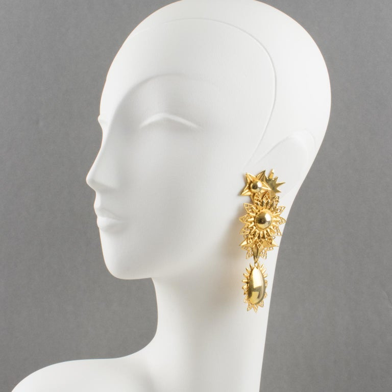 Charming Zoe Coste gilt metal dangling clip-on earrings. Featuring stars and suns carved design with gilt metal all textured and ornate. Unusual design from that famous French designer, creator of Reminiscence brand. Marked underside