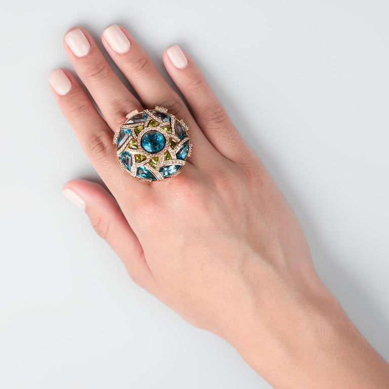 With an extensive array of gorgeous Peridot and Blue Topaz, this White Diamond lined disc style cocktail ring is truly a one of a kind Zorab Creation.  All delicately placed, this 15.55 carat Blue Topaz and 2.22 Peridot comes together to beautifully