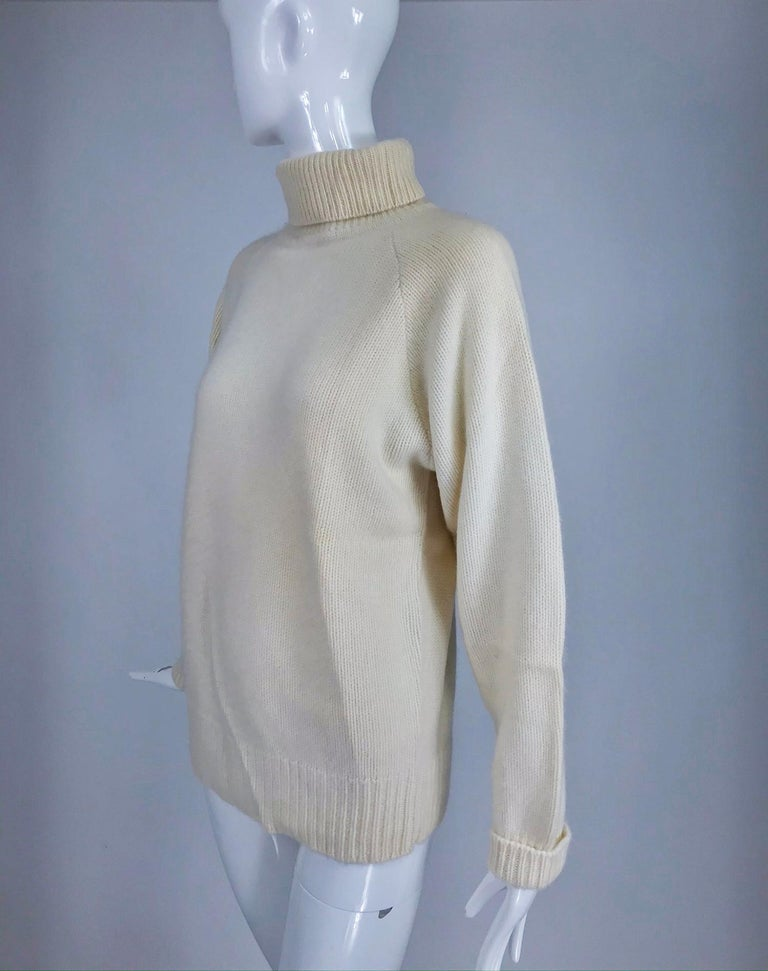 Zoran off white chunky cashmere turtleneck sweater from the 1990s. Pull on sweater with raglan sleeves. Neck, cuffs and hem of ribbed knit. This sweater has been packed away in cold storage for a while, the creases seen in the photos will fall out