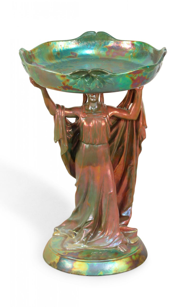 Art Nouveau Zsolnay porcelain green iridescent eosin centerpiece with female figure holding round tray above head.